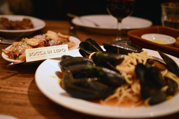 Bocca di Lupo's addictive 'nduja orrechiette and mussels spaghetti, with a plate of homemade sausages in the background