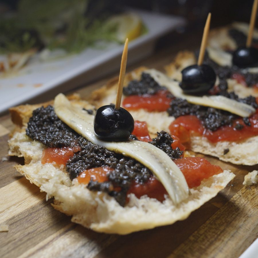 Coca toast topped with tomato purée and olive tapenade,white anchovies.